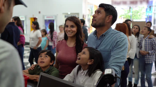 Happy latin american young couple with their kids choosing snacks at the concession stand at the cinema video