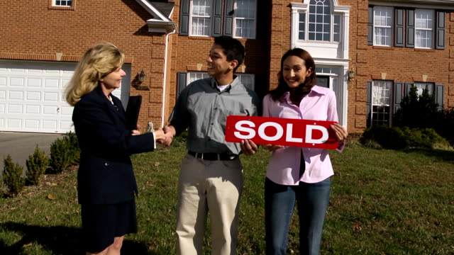 Happy Latin Couple with Agent Holding a SOLD Sign video
