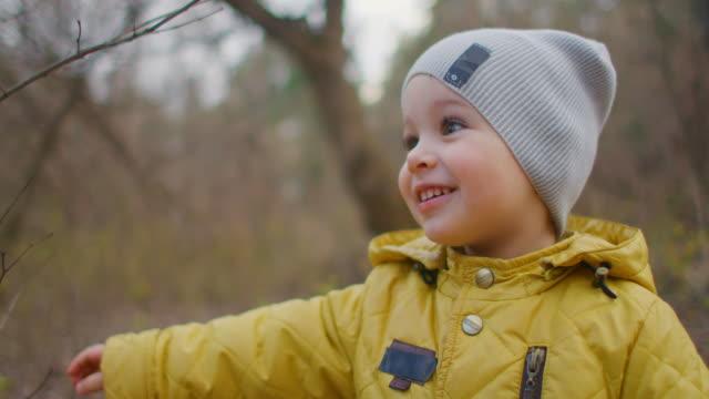 glücklich lachend und lächelnd junge 2 jahre alt im wald schaut in die kamera. charmante niedliche junge mit großen wimpern. ein junge in gelber jacke und hut - laub winter stock-videos und b-roll-filmmaterial