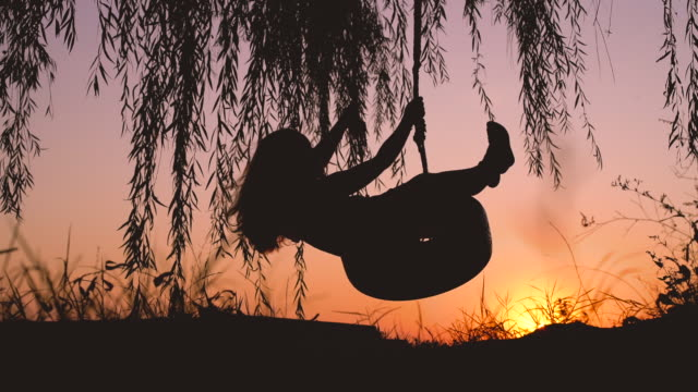 Happy laughing child girl on swing in sunset summer video