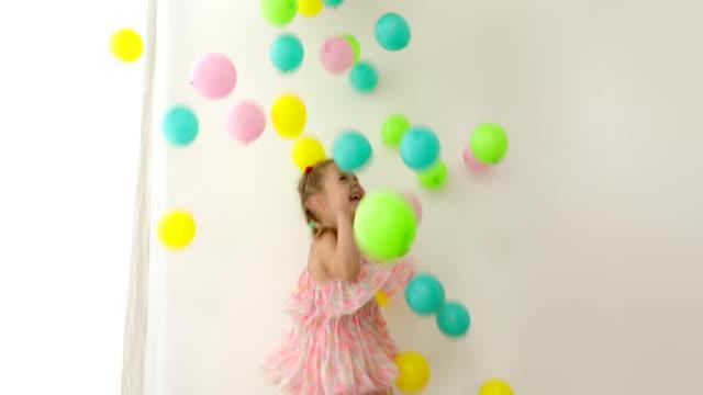 lycklig skrattande flicka i rosa klänning spridning mångfärgade ballonger - förskoleelev bildbanksvideor och videomaterial från bakom kulisserna