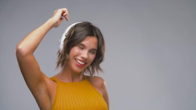 lycklig skratta ung kvinna i hörlurar dans - latino music bildbanksvideor och videomaterial från bakom kulisserna