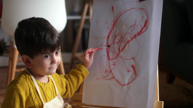 Happy little baby artist drawing with colorful paints at home