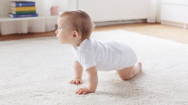 happy little baby crawling in living room at home childhood, babyhood and people concept - happy little baby crawling on carpet in living room at home crawling stock videos & royalty-free footage