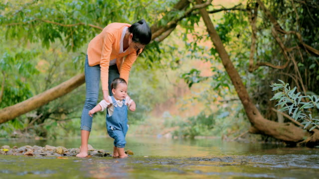 Happy little baby learning to walk with mother help on nature walk by canal.Happy loving family.Family Relationship,Asian family,Life insurance.Relations and People,Childhood and parenthood concept.South East and East Asia: Asian Babies.Baby's First Steps - vídeo