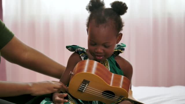 Happy little black girl playing guitar with mum in bedroom room.