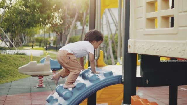 lycklig liten pojke ner glida i parken - förskoleelev bildbanksvideor och videomaterial från bakom kulisserna