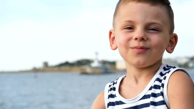 夏の海の背景の縞模様のシャツで幸せの小さな男の子 - 4歳から5歳点の映像素材/bロール
