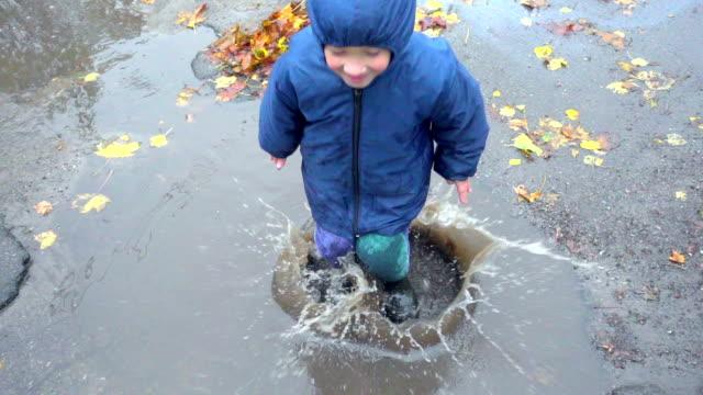 vídeos de stock e filmes b-roll de happy little boy jumping in muddy puddle, slow motion - poça