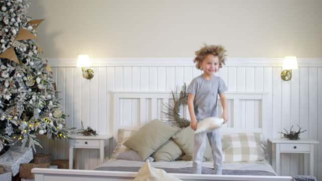 Happy Little Boy Jumping on Bed beside Christmas Tree