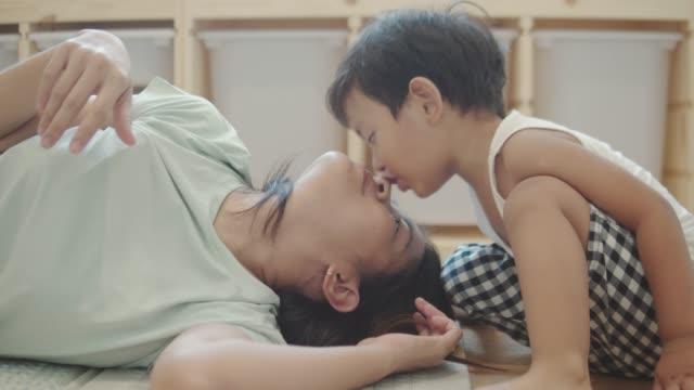 幸せな小さな男の子は、朝のベッドで母をキス - 家族 日本人点の映像素材/bロール