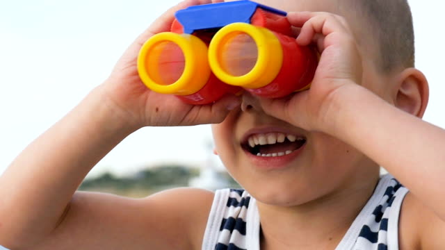happy little boy looking far away through binoculars video