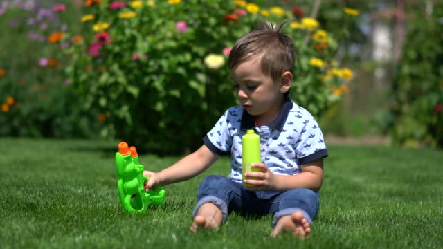 Happy little boy playing with water gun on grass