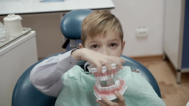 happy little boy plays with plastic form of human jaw in dentist chair - dentist stock videos & royalty-free footage