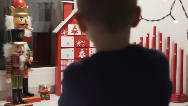 glücklich kleine junge nimmt süß aus advent kalender haus form mit weihnachten nussknacker im hintergrund. - advent stock-videos und b-roll-filmmaterial