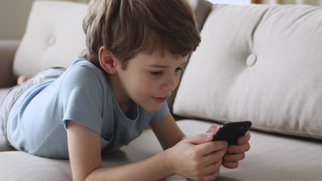 Happy little child boy playing on mobile online games. Addicted to technology happy little child boy lying on comfortable sofa, playing on mobile online games alone at home. Adorable small kid son using smartphone, watching funny videos in social media. effortless stock videos & royalty-free footage