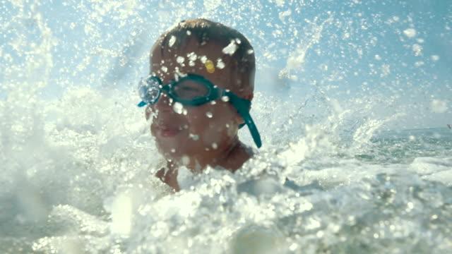 Happy little child enjoying water splashing video