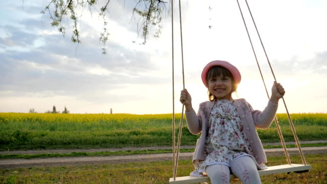 happy little child have fun sway spin on swing on nature sunset, female kid swaying, in forest park, children on swing - oscillare video stock e b–roll
