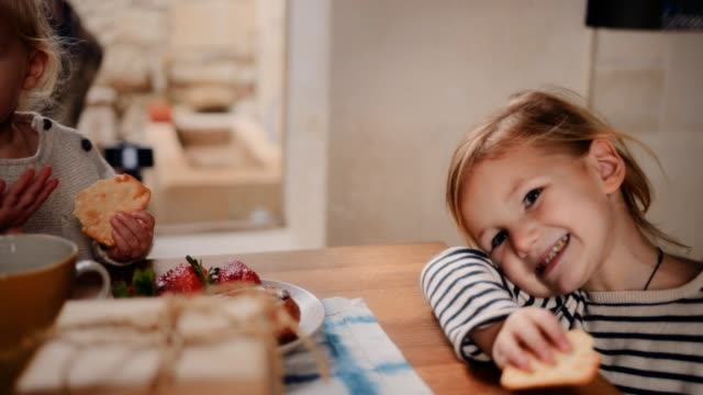 Happy little children eating healthy snack at home Happy little girls eating healthy breakfast with strawberries sitting around kitchen table at home snack stock videos & royalty-free footage