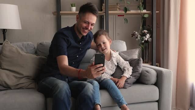 Happy little cute girl using funny mobile apps with dad.