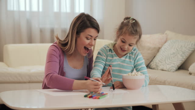 vídeos de stock e filmes b-roll de happy little girl and her mother drawing on the paper and having fun together. - mãe solteira