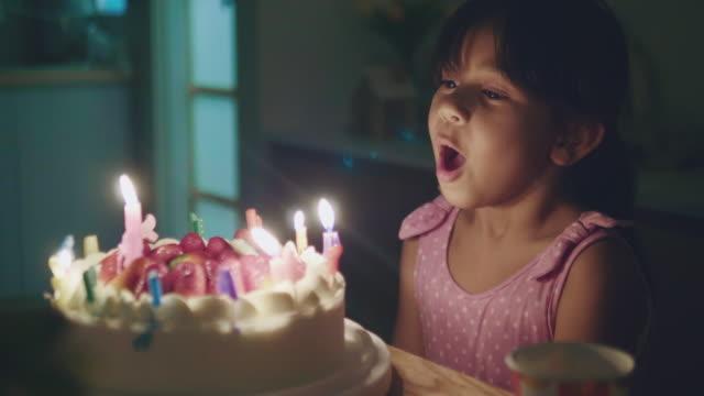glückliches kleines mädchen bläst kerzen auf einem geburtstagstorte - kerze stock-videos und b-roll-filmmaterial