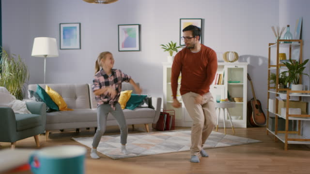 Happy Little Girl Dances with Young Father in the Middle of the Living Room. Happy Family Time, Father and Daughter Dancing at Home.