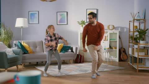 vídeos y material grabado en eventos de stock de danzas de chica poco feliz con el joven padre en medio de la sala de estar. feliz tiempo de familia, padre e hija bailando en casa. - bailar