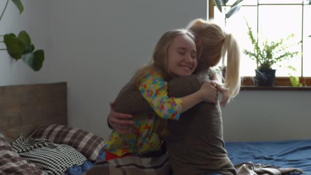 mutlu küçük kız annesi kucaklayan sonra uyanık - ultra yüksek çözünürlüklü televizon stok videoları ve detay görüntü çekimi