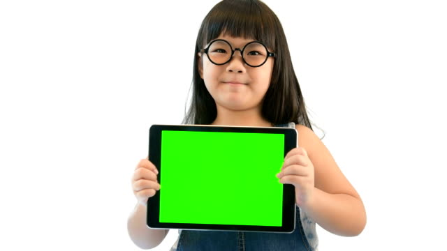 Happy little girl holding green screen tablet PC on white screen video