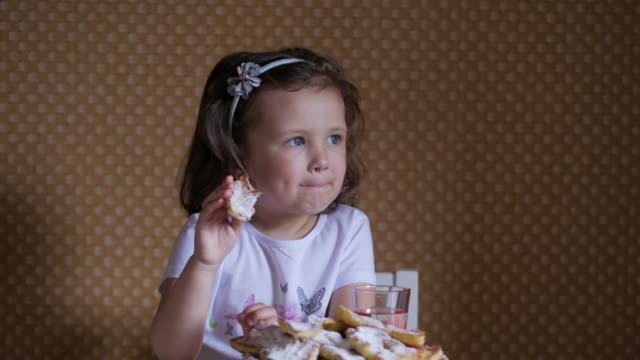 happy little girl in white t-shirt sitting at table and eating homemade cakes. concept of sweet food and children. - maglietta bianca video stock e b–roll