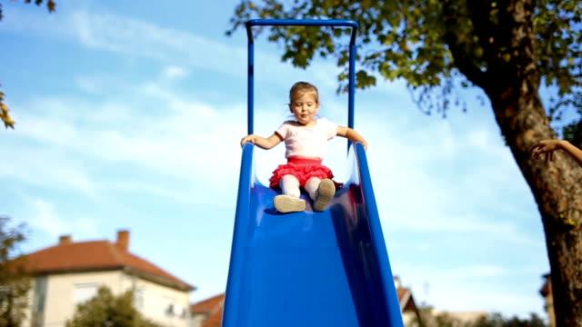 Happy little girl on slide in park video