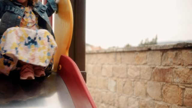 happy little girl playing and having fun on playground slide - slitta video stock e b–roll
