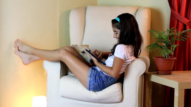 Happy little girl playing on a tablet at home video