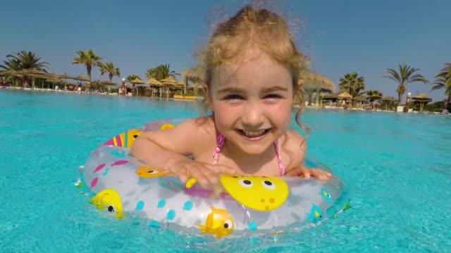 lycklig liten flicka leker med färgglad uppblåsbar ring i utomhuspoolen på varm sommardag.  barnen leker i tropiska resort.  barnen lär sig att simma. barnvänlig strandsemester. - inflatable ring bildbanksvideor och videomaterial från bakom kulisserna