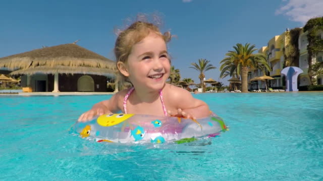 Happy little girl playing with colorful inflatable ring in outdoor swimming pool on hot summer day.  Children play in tropical resort.  Kids learn to swim. Family beach vacation.
