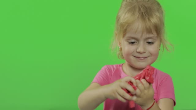 Happy little girl plays with plasticine on chroma key background