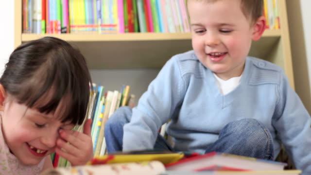 glückliches kleines mädchen lesen geschichte zu ihren bruder - grundschule stock-videos und b-roll-filmmaterial