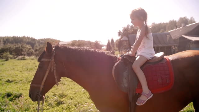 a happy little girl riding a horse in the nature on a sunny day. she is smiling, having fun. slow mo - briglia video stock e b–roll