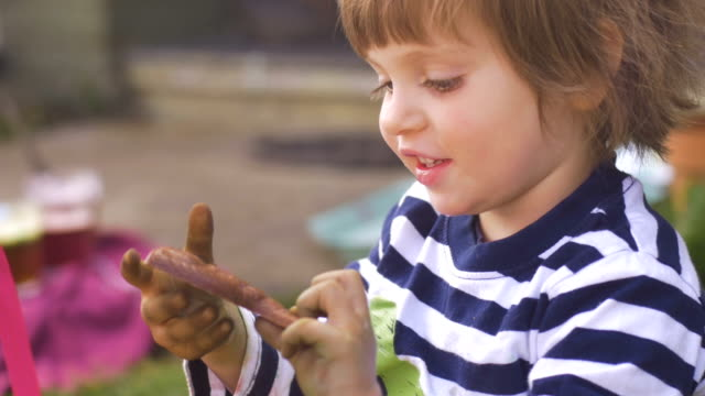 Happy little girl taking a bite of chocolate outside in slow motion video