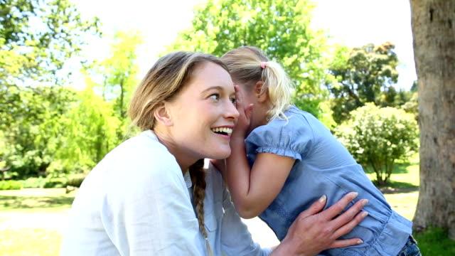 Happy little girl telling mother a secret in park video