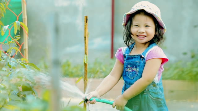 Happy little girl watering plant in garden \\ Concept : taking care of nature - Vidéo