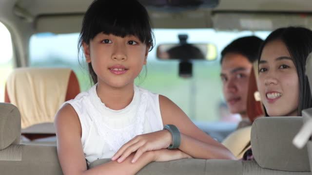 キャンピングカーで道旅行や夏の休暇を楽しむために車に座っているアジアの家族との幸せな女の子 ビデオ