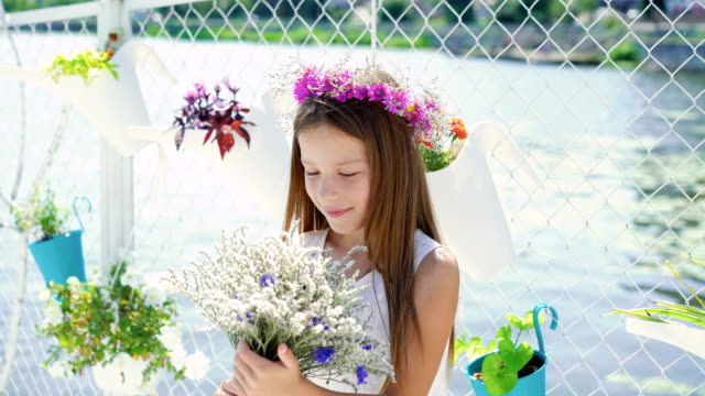 Happy little girl with bouquet of flowers looking around on sunny day. FullHD video