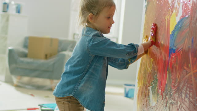 happy little girl with hands dipped in vivid paint draws colorful abstractions on the wall. she is having fun and laughs. home is being renovated. - birichinata video stock e b–roll