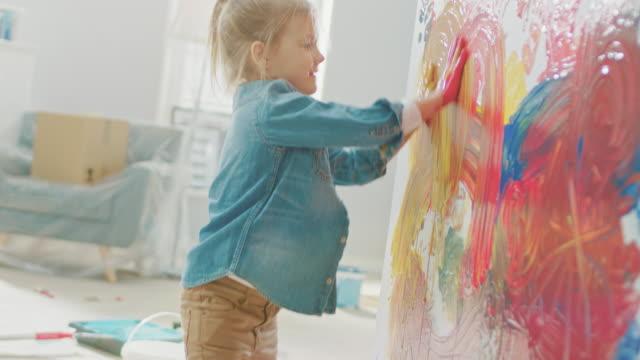 손으로 벽에 선명한 페인트 무 화려한 추상 미술에 행복 한 어린 소녀. 그녀는 재미와 웃음입니다. 홈 개조 되 고 있다입니다. - kids drawing 스톡 비디오 및 b-롤 화면