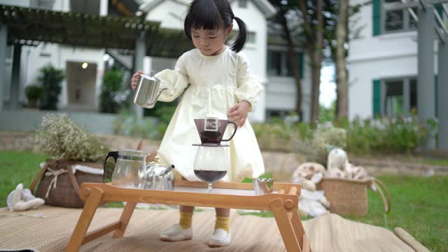 A happy little toddler is making coffee in the garden .
