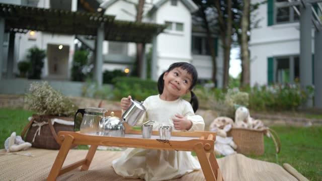 ็Happy little toddler is making coffee in the garden .