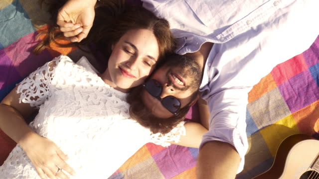 Happy lovely young couple lying on colorful blanket in the park looking at the sky pointing clouds romantic with guitar sunglasses beautiful attractive girl top view rotating camera slow motion video