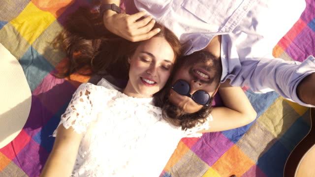 空のポイントを見て公園でカラフルな毛布の上に横たわる幸せな素敵な若いカップル雲ギター サングラスとのロマンチックな美しい魅力的な女の子トップ ビュー カメラ スローモーションを回転 - ピクニック点の映像素材/bロール
